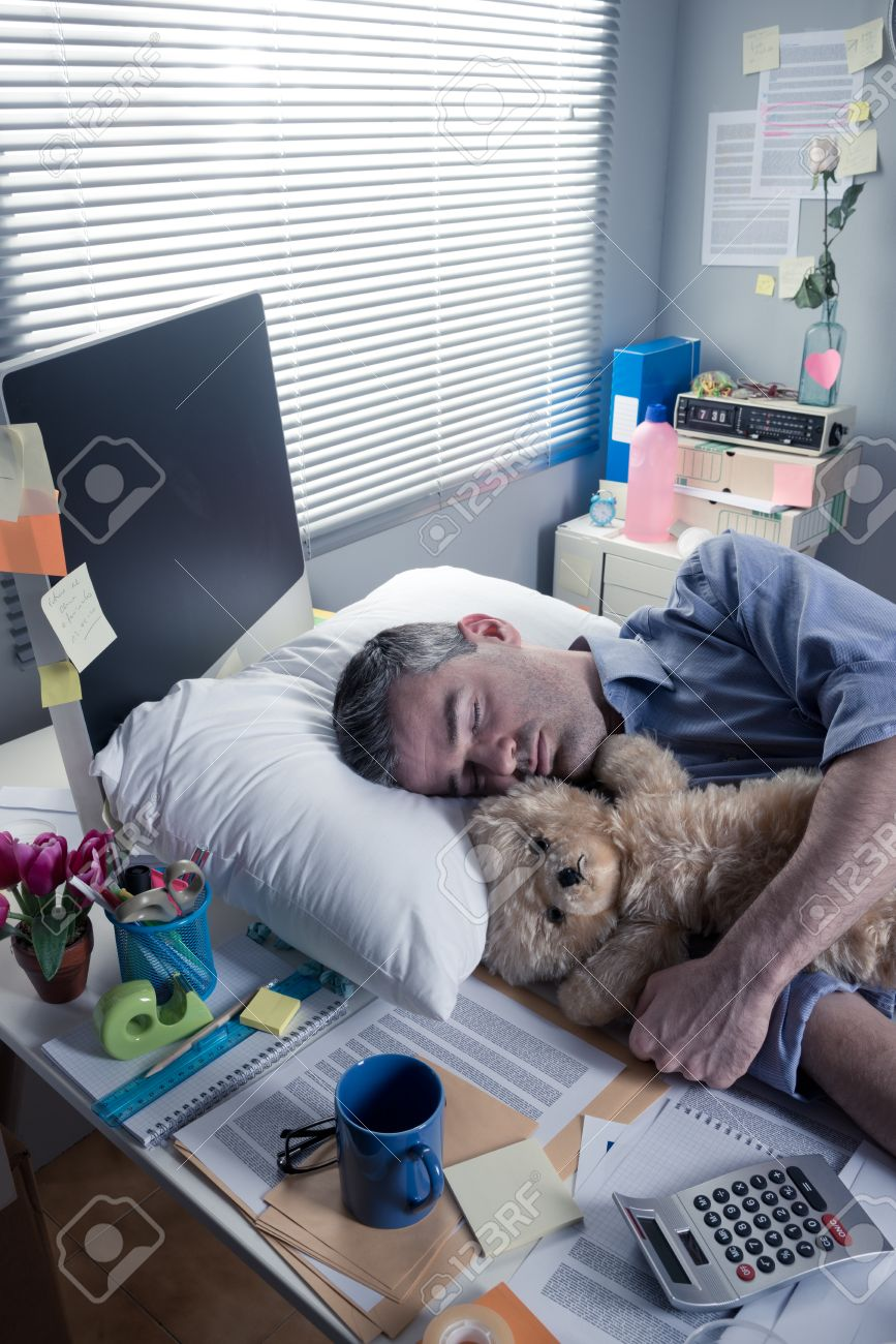 Funny office worker sleeping in the office overnight with teddy bear. Stock Photo - 33142821