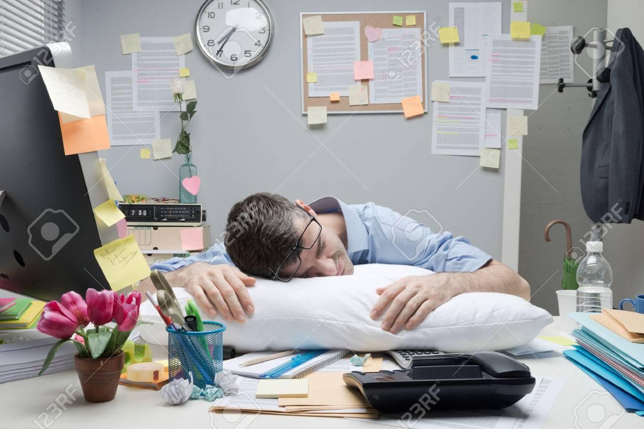 Fatigué employé de bureau de dormir sur un oreiller sur son bureau