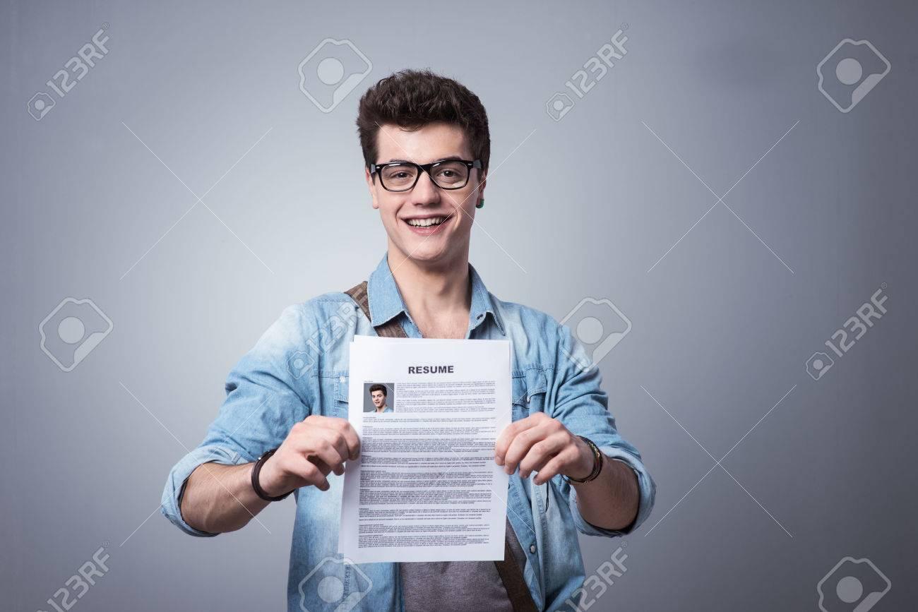 Jeune homme souriant tenant son CV pour postuler à un emploi Banque d'images - 36529711