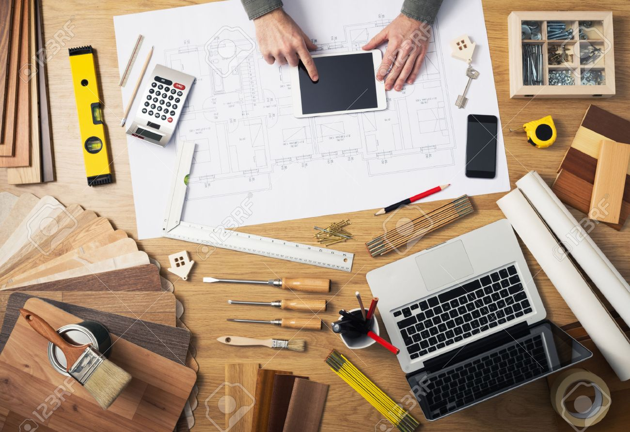 Construction engineer and architect's desk with house projects, laptop,  tools and wood swatches top