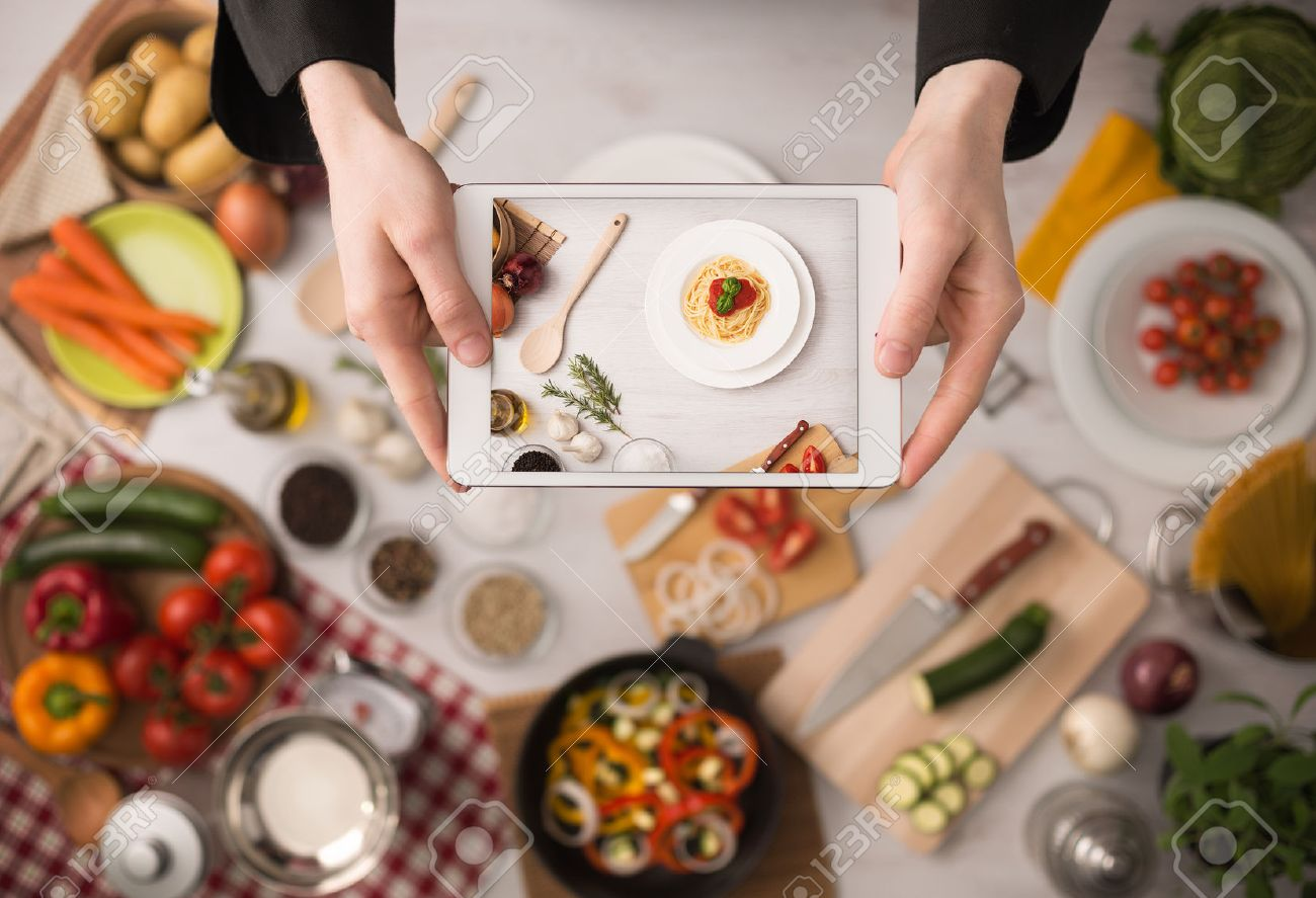 Kitchen Table With Food cook's hands holding a touch screen tablet close up, kitchen