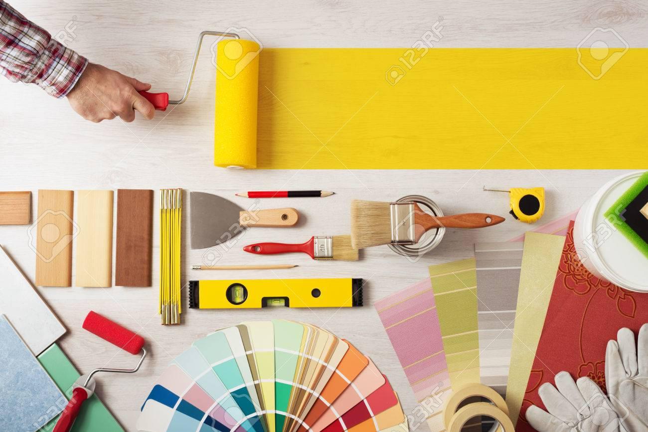 Decorador Celebración De Un Rodillo De Pintura Y La Pintura De Una ...