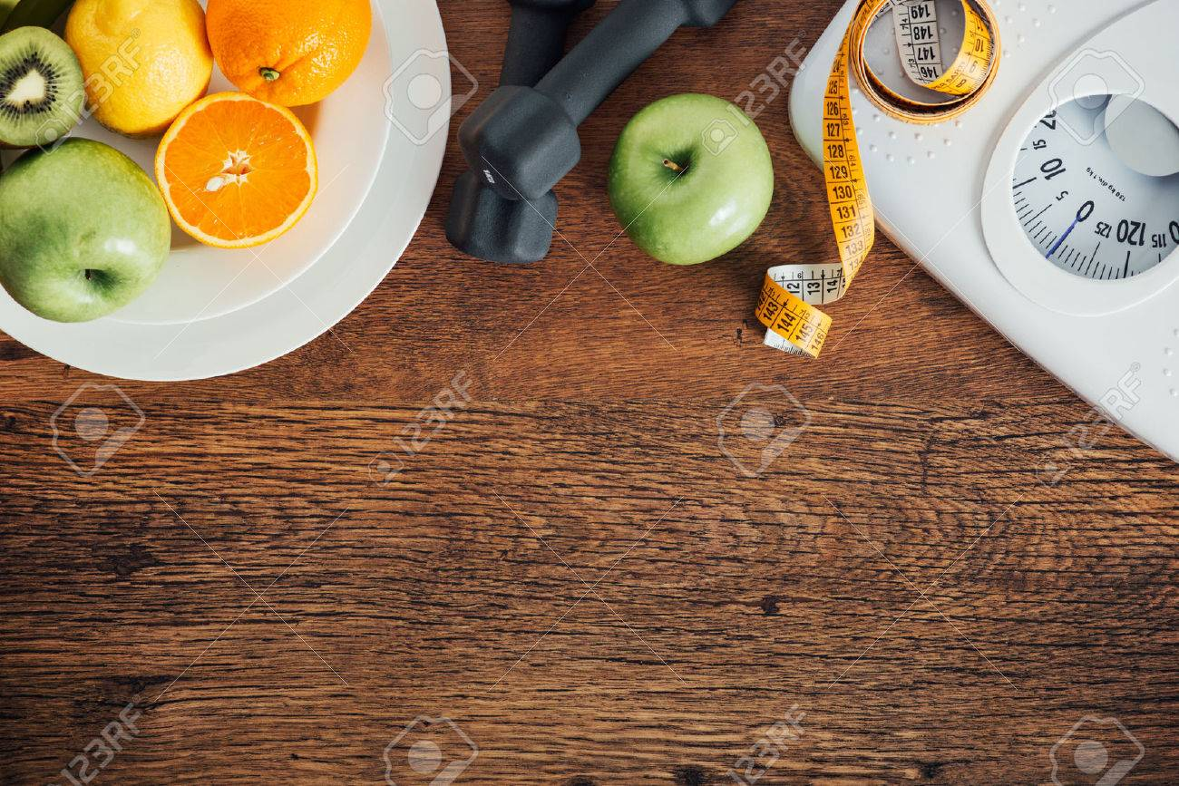 Fitness and weight loss concept, dumbbells, white scale, fruit and tape measure on a wooden table, top view Stock Photo - 42512518