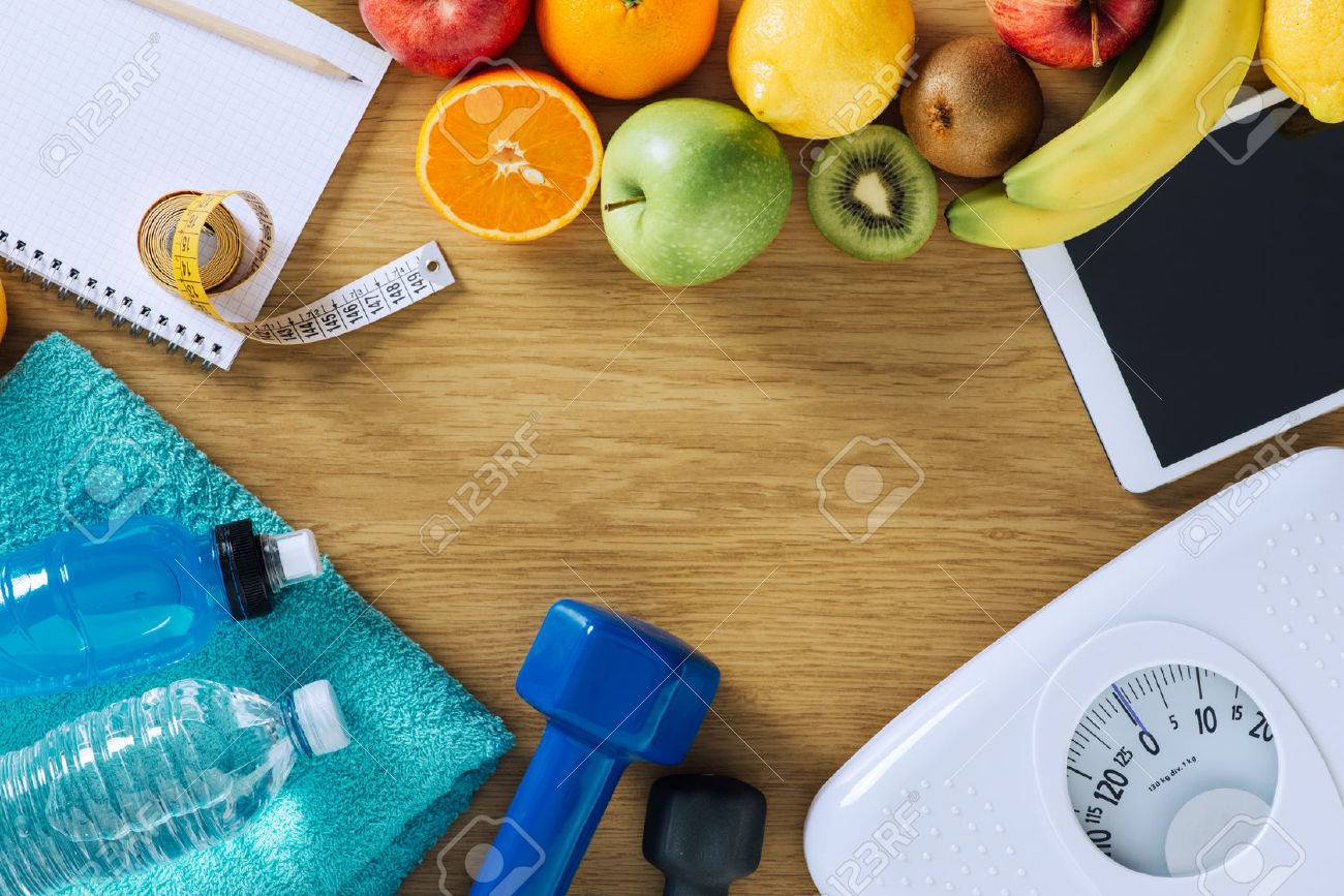 Fitness and weight loss concept, dumbbells, white scale, towels, fruit, tape measure and digital tablet on a wooden table, top view Stock Photo - 42512520