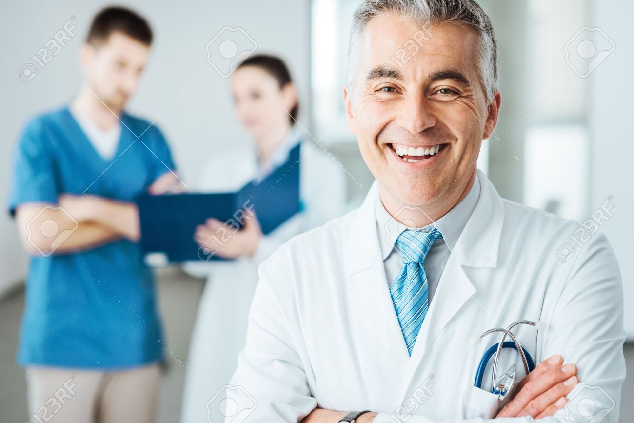 Confident doctor posing and smiling at camera and medical staff checking medical records on background Stock Photo - 44950828