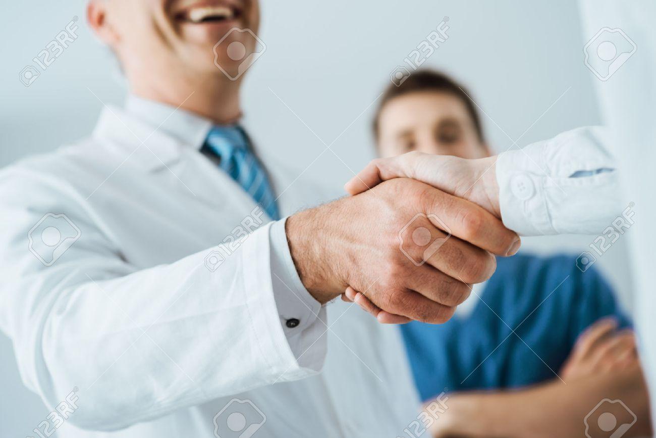 Professional doctors handshaking at hospital hands close up professional doctors handshaking at hospital hands close up agreement and hiring concept stock photo platinumwayz