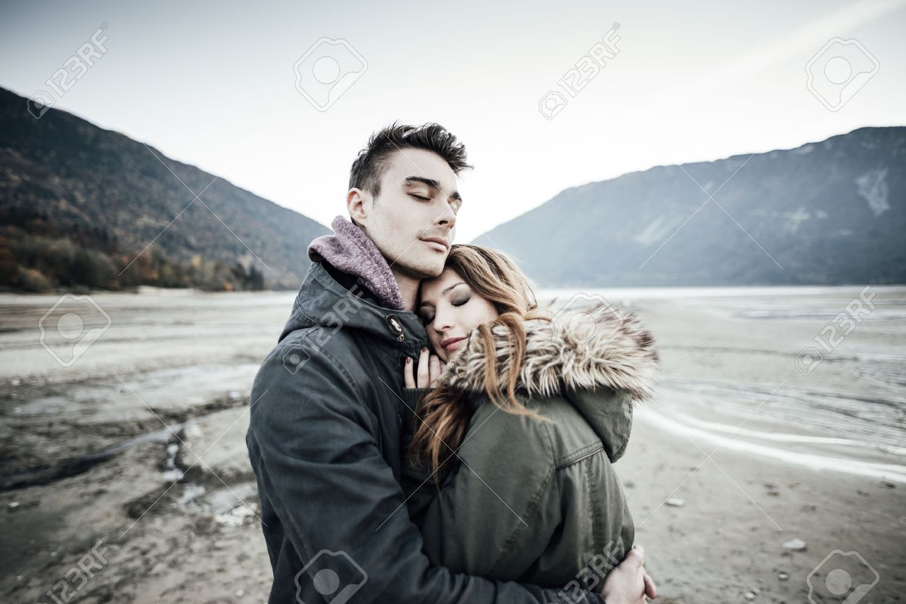Young loving couple hugging, lake and mountains on background, love and romance concept - 50768730