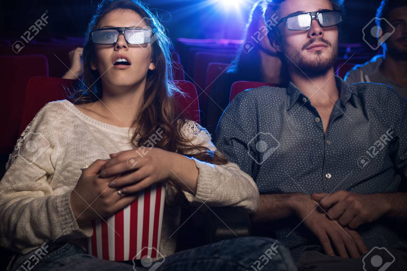 Young teenagers at the cinema wearing glasses and watching a 3d movie, a girl is eating popcorn, entertainment and movies concept - 51616744