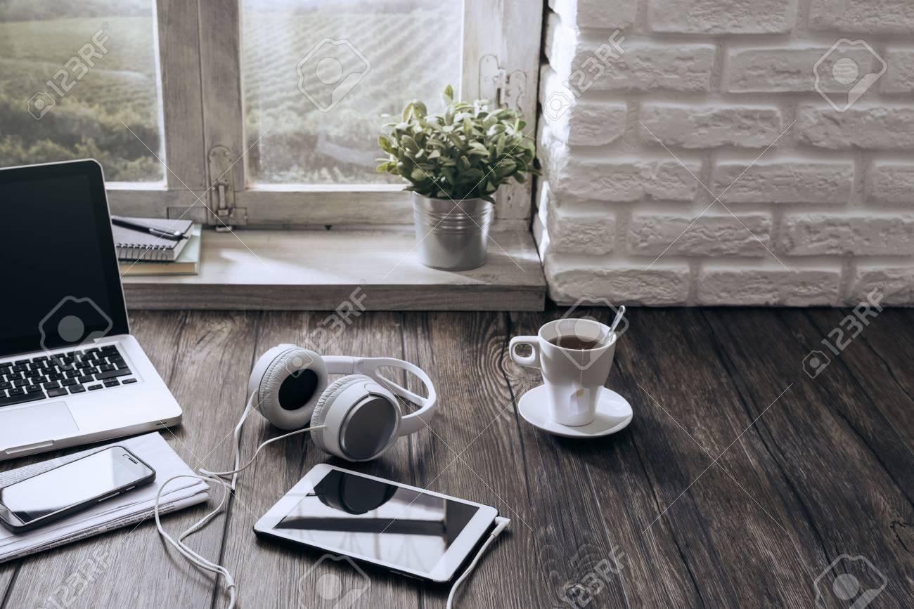 Ordinateur portable tablette et écouteurs sur un bureau en bois à