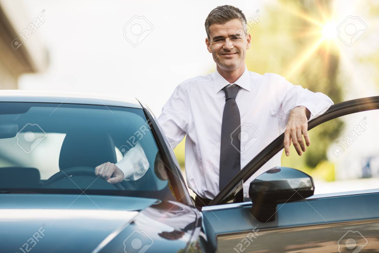 Businessman leaning on the car door and smiling at camera, dealership and business concept - 67106148