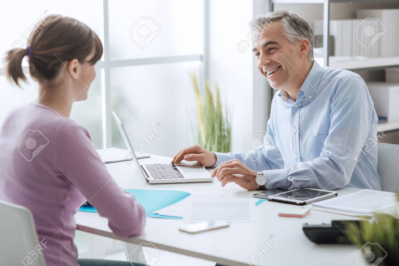 Confident advisor meeting with a customer in his office, he is explaining a contract document and policy to the woman sitting at his desk - 70830970