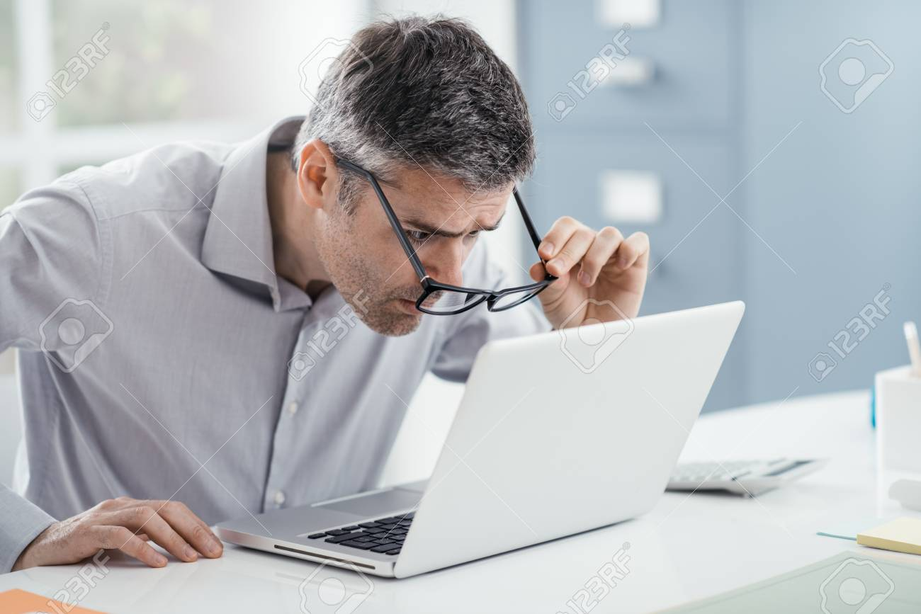 Businessman working at office desk, he is staring at the laptop screen close up and holding his glasses, workplace vision problems - 88364332