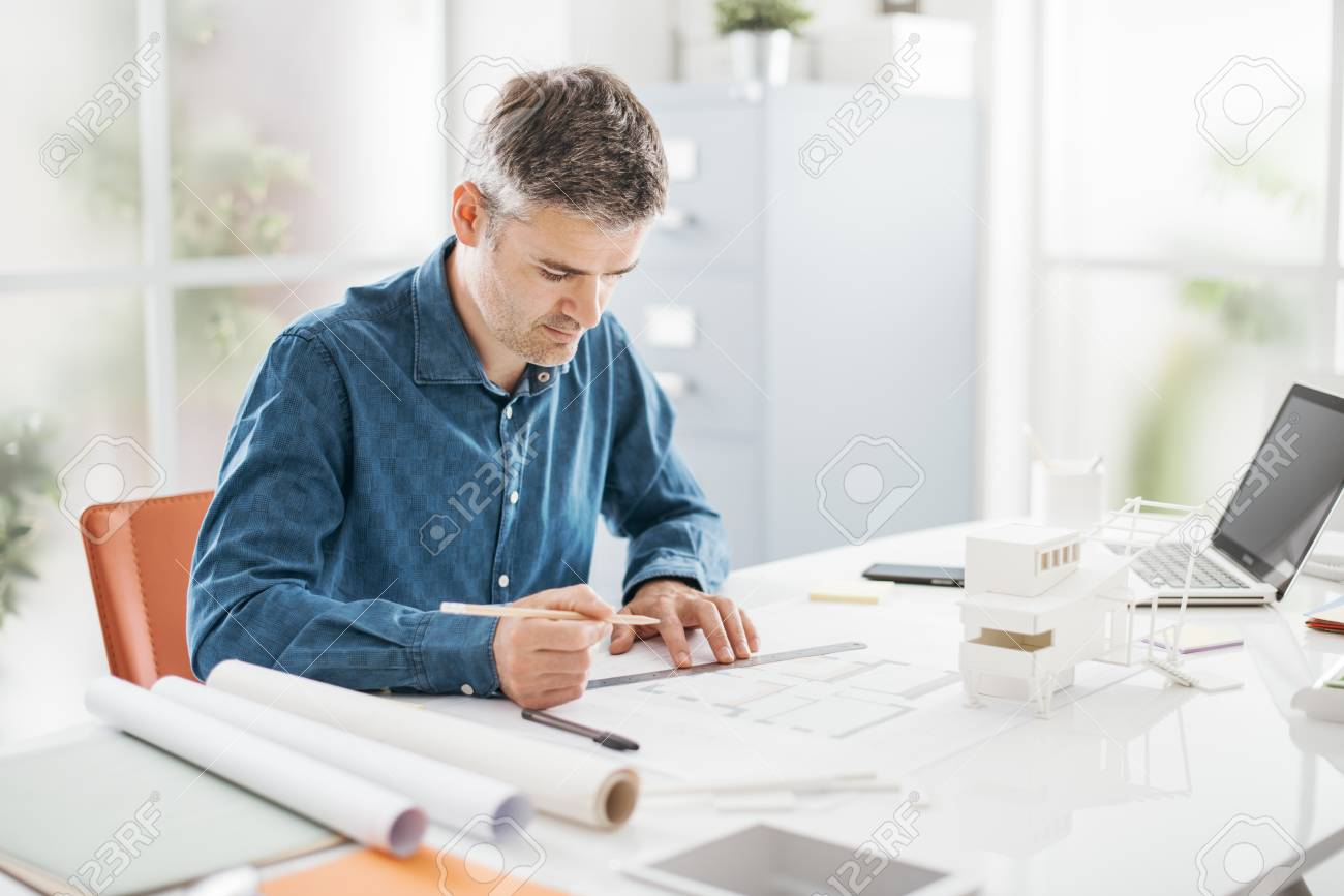 Professional architect working at office desk, he is drawing and making measurements on a project blueprint, design and architecture concept - 88364395