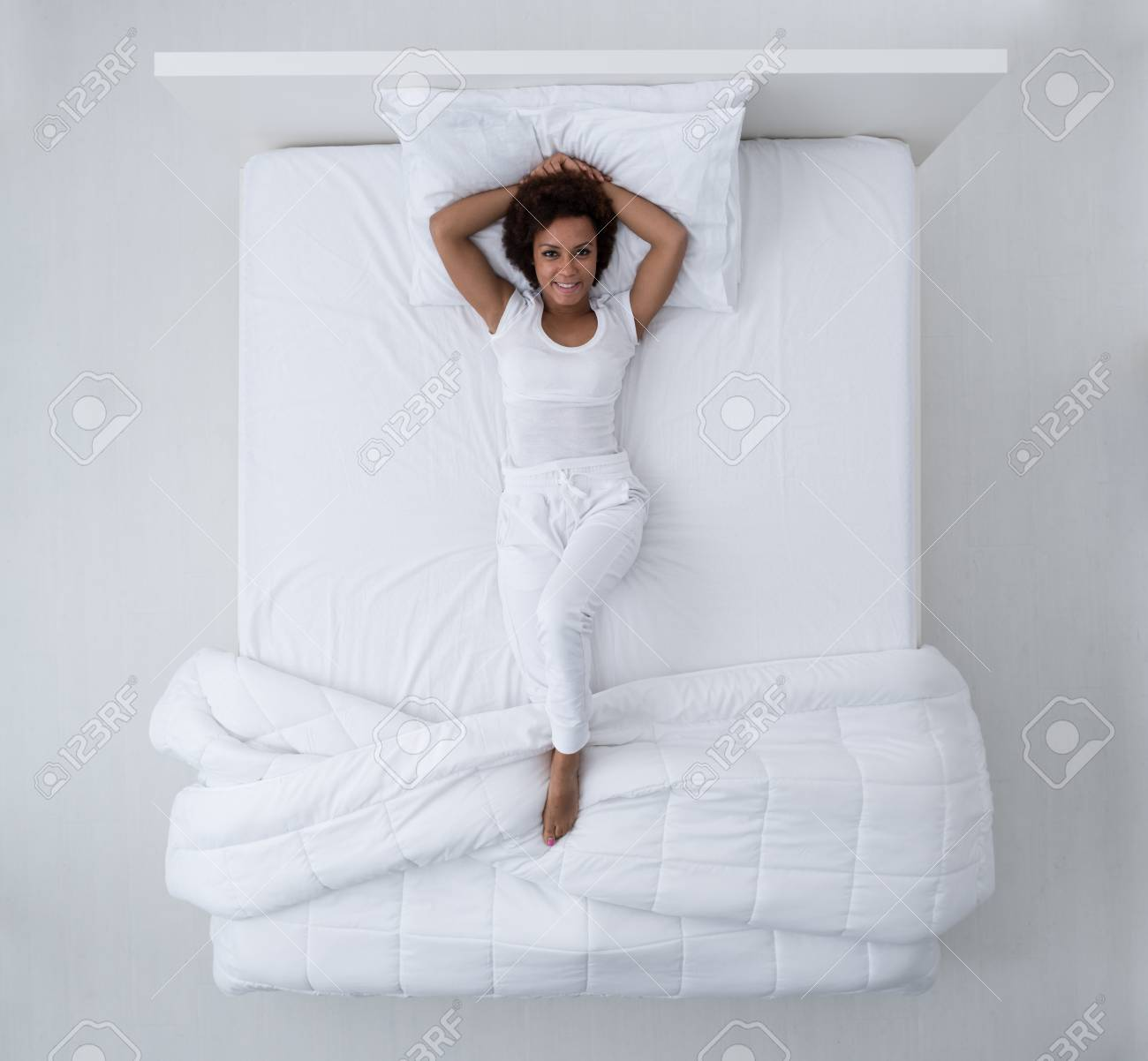 Beautiful african american woman lying in bed and smiling at camera, top view - 88260806