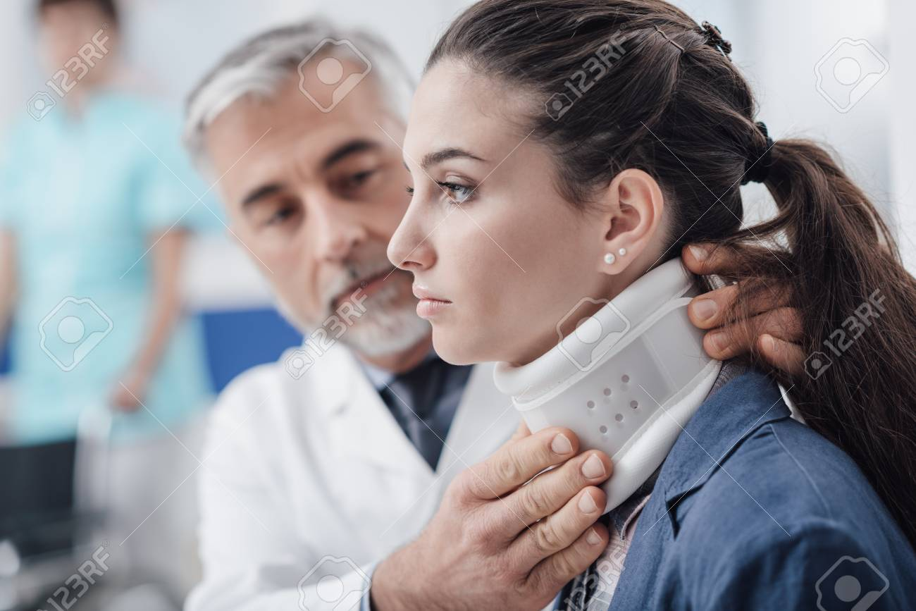 Professional doctor visiting a young injured patient at the hospital, he is adjusting her cervical collar - 92039080
