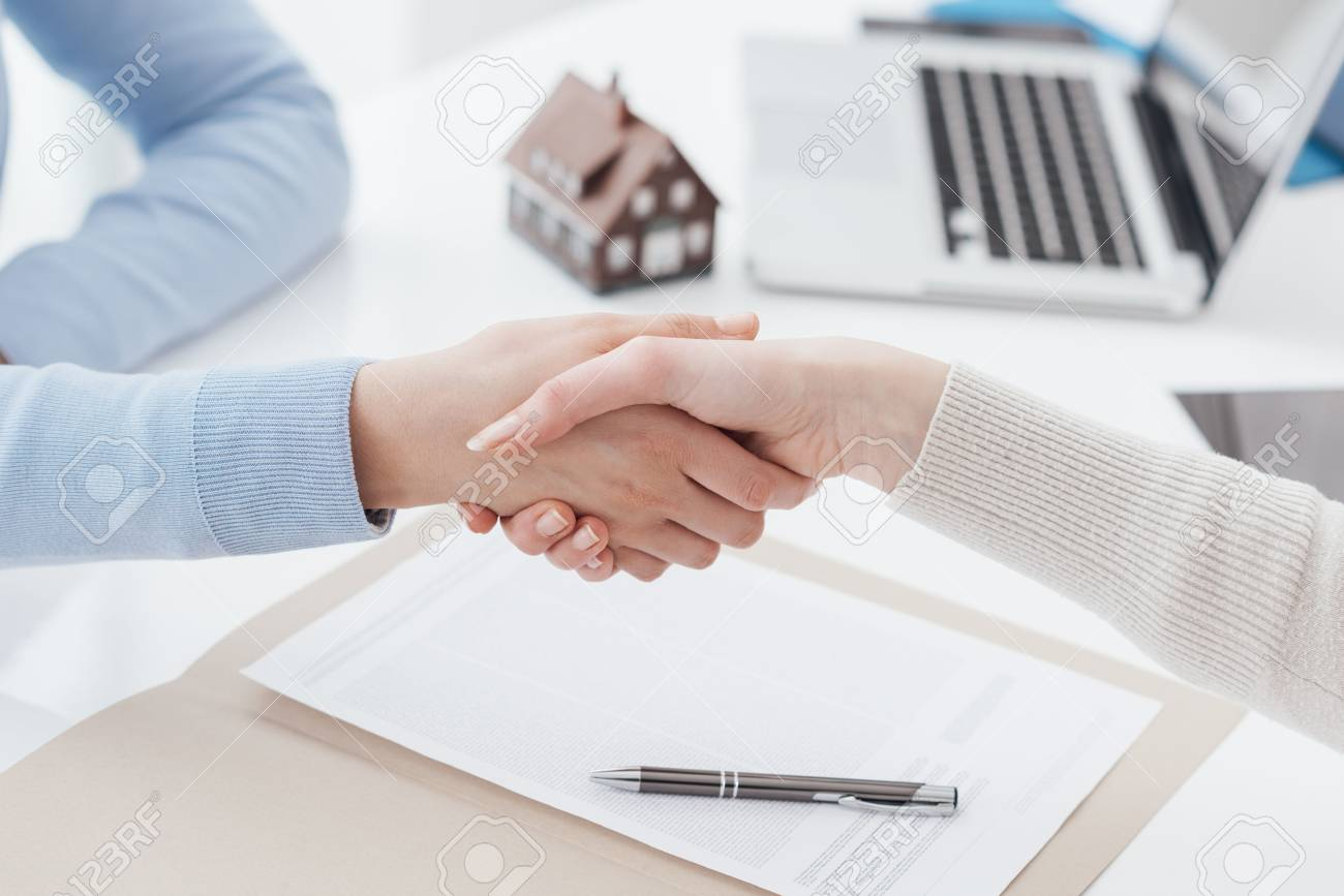 Insurance agent and customer shaking hands after signing a contract: real estate, home loan and insurance concept - 91831708
