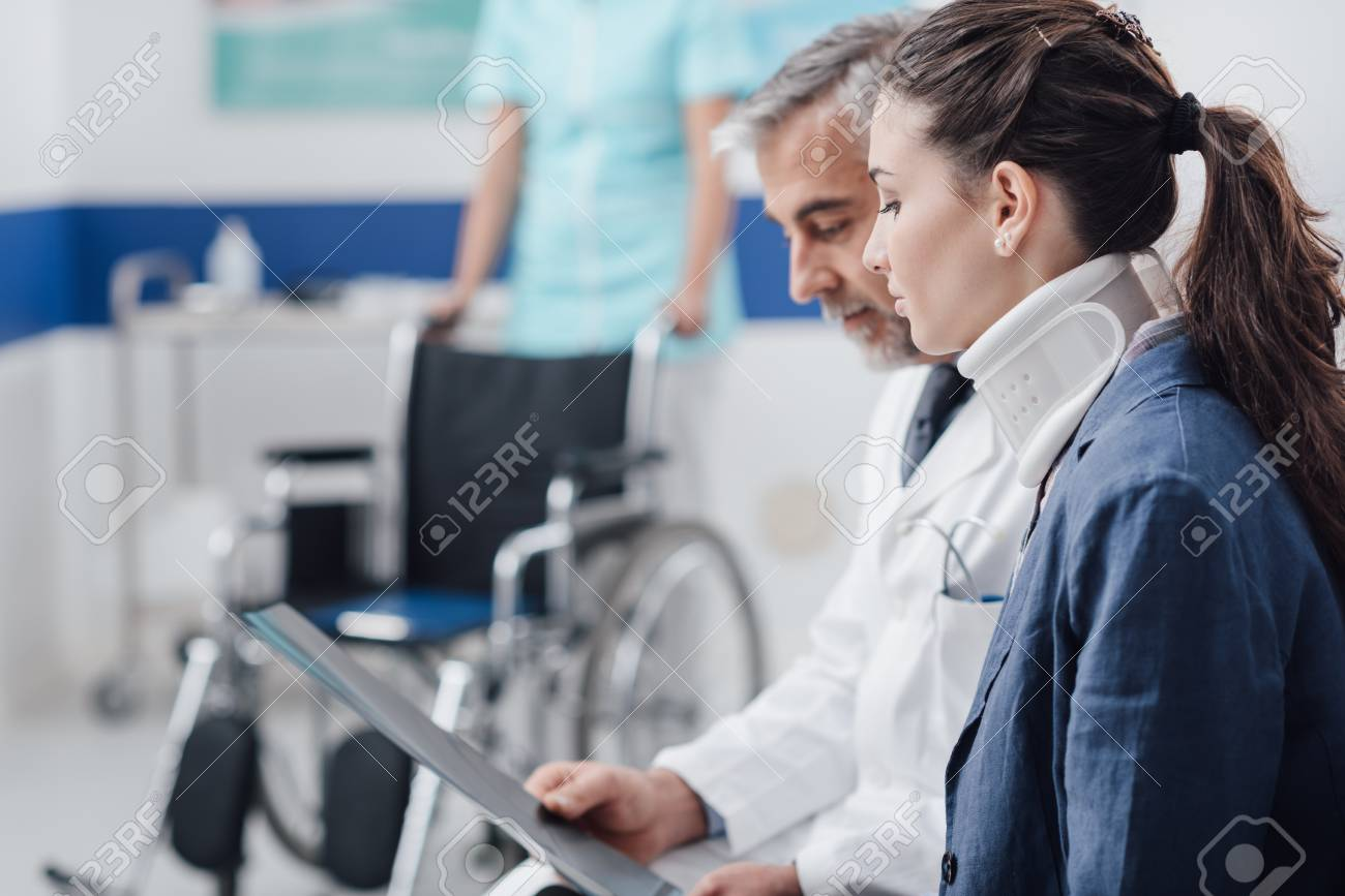 Doctor examining x-ray and medical records of an injured young patient with cervical collar and nurse pushing a wheelchair on the background - 92026342