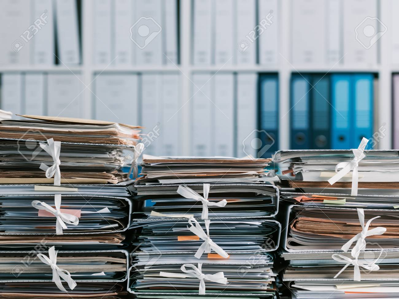 Stacks of files and paperwork in the office and bookshelves on the background: management and storage concept - 95237494