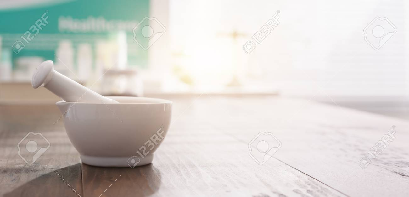 Mortar and pestle on the pharmacist's table and pharmaceutical products on the background - 98231407