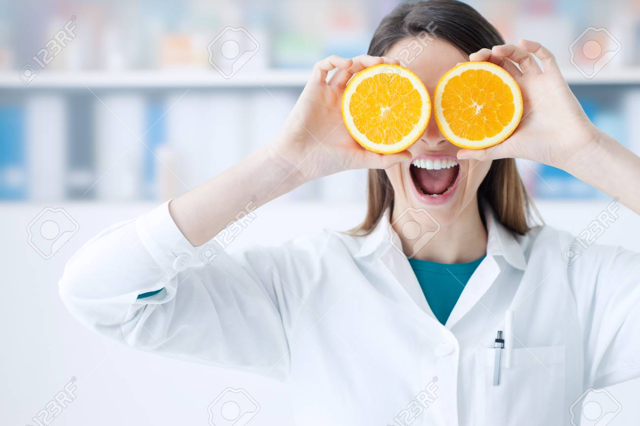 Funny female dietist holding oranges over her eyes, diet and nutrition concept - 100718108