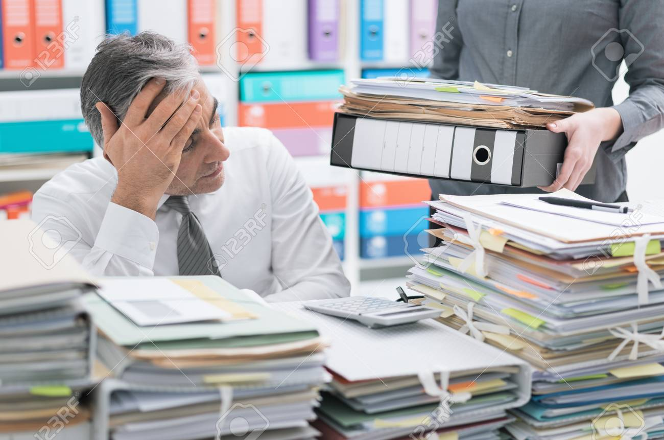 Stressed businessman working at office desk and overloaded with work, the desktop is covered with paperwork, his secretary is bringing more files - 101210305
