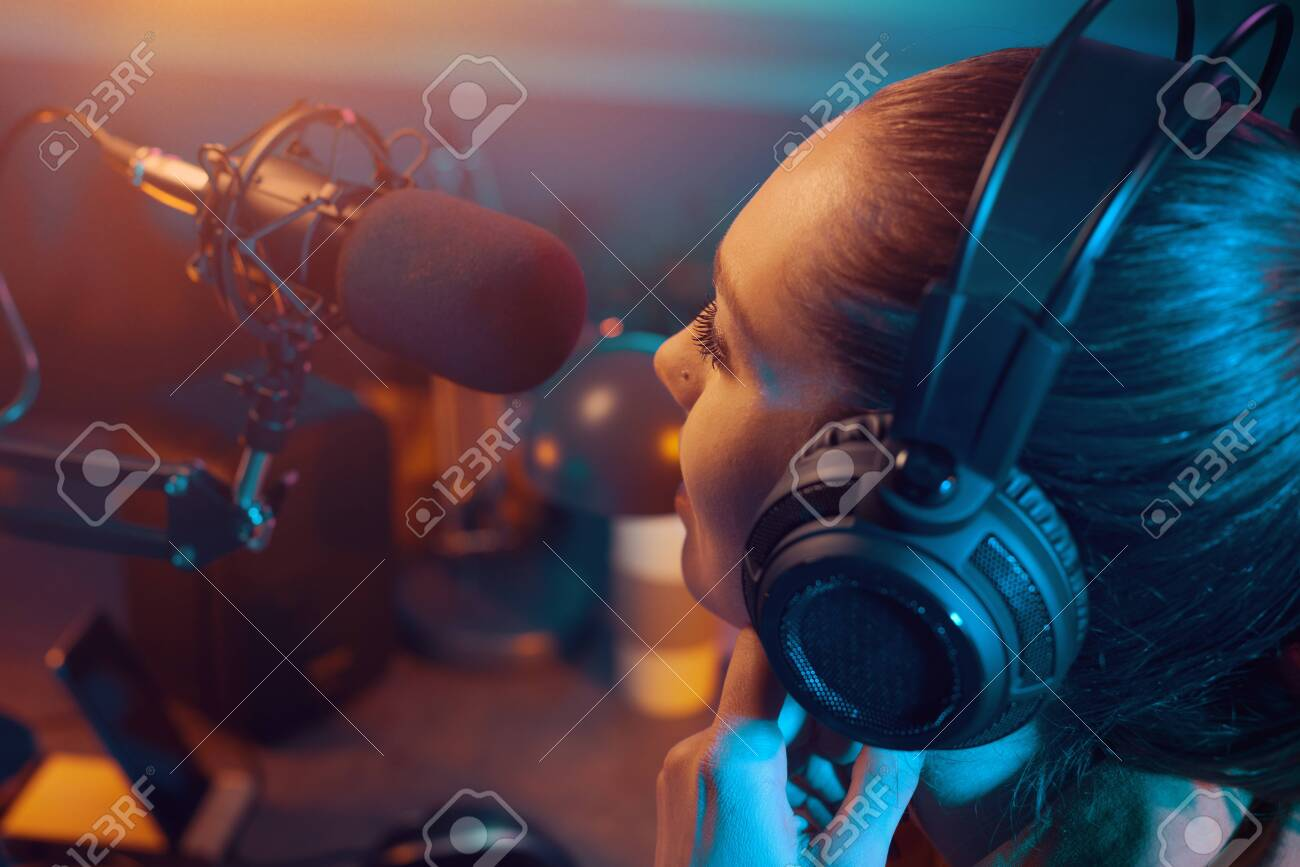 Young charming radio dj working in the studio, she is talking into the microphone, entertainment and communication concept - 144810286