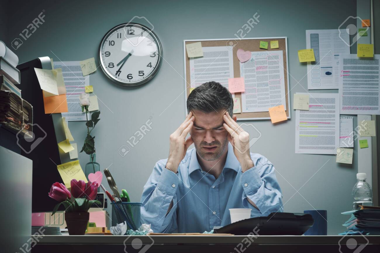 Tired office worker at desk with headache touching his temples. - 145886394