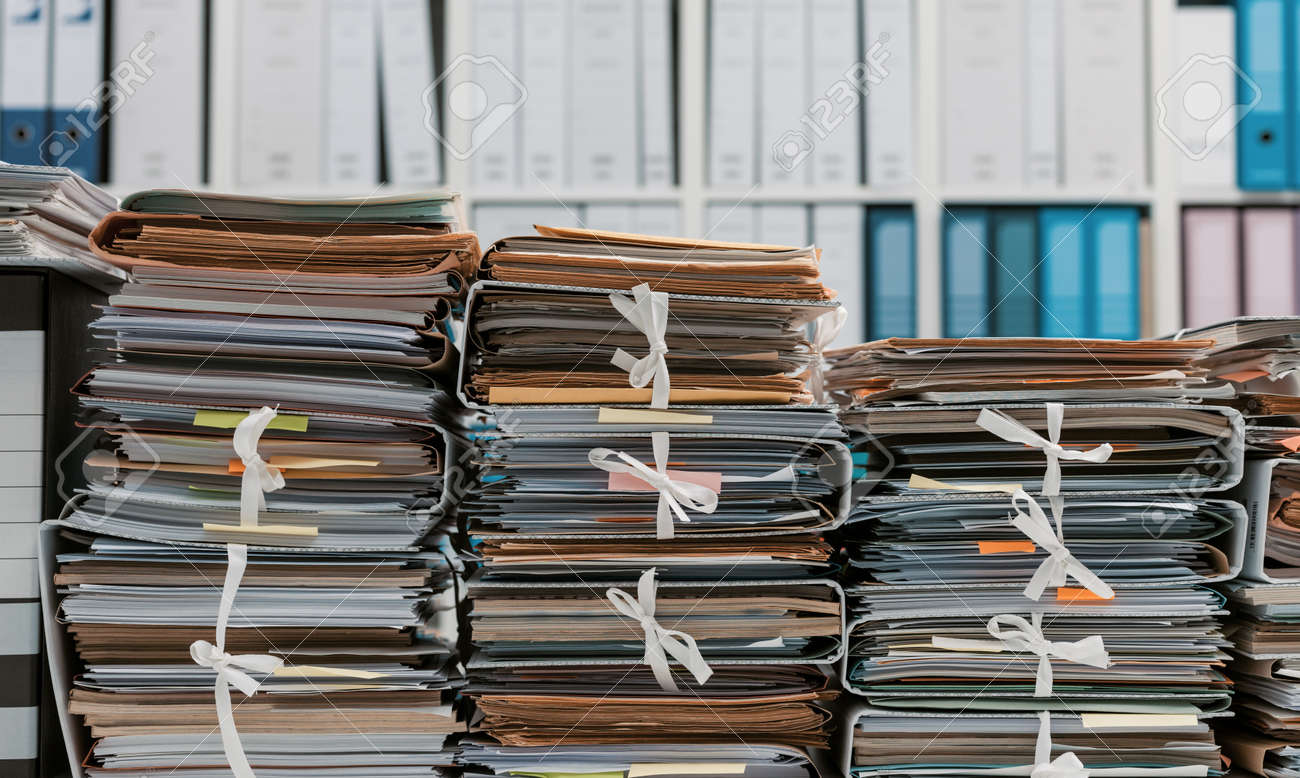 Stacks of files and paperwork in the office and bookshelves on the background: management and storage concept - 145893334