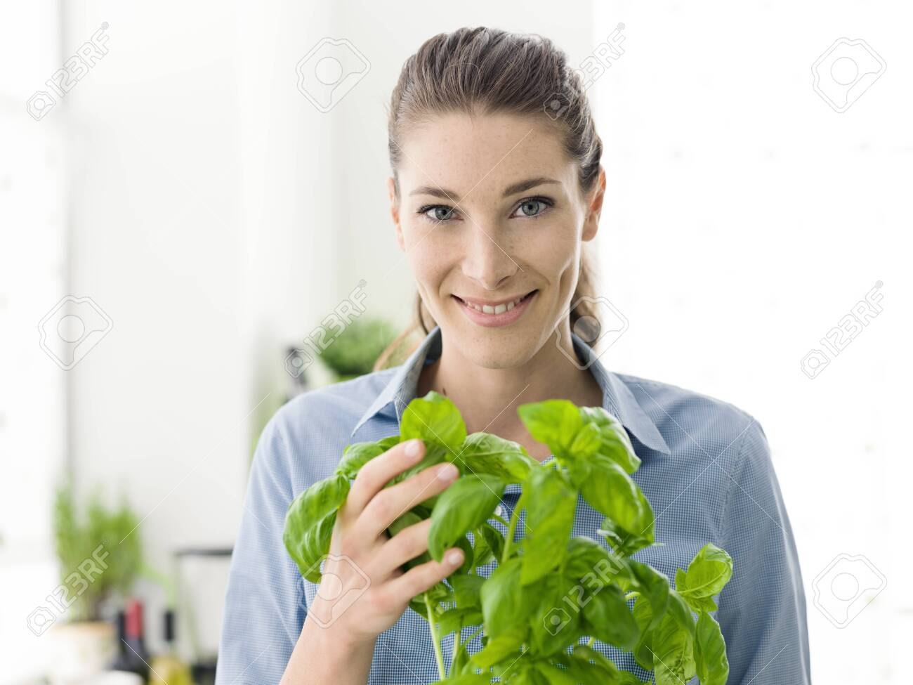 Young woman growing fresh herbs at home, she is holding a plant of basil and smiling at camera - 145967087
