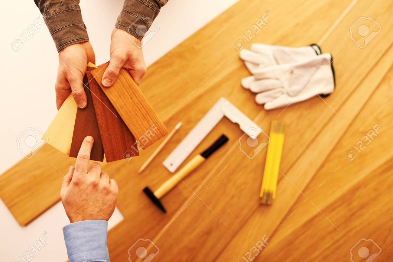 Carpenter showing some wooden baseboard swatches to a customer and choosing a color, flooring installation and work tools on background - 146439941