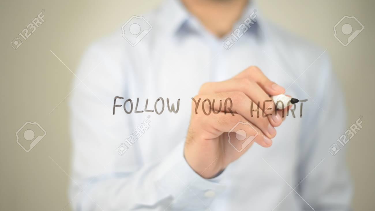 Follow Your Heart Man Writing On Transparent Screen Stock Photo