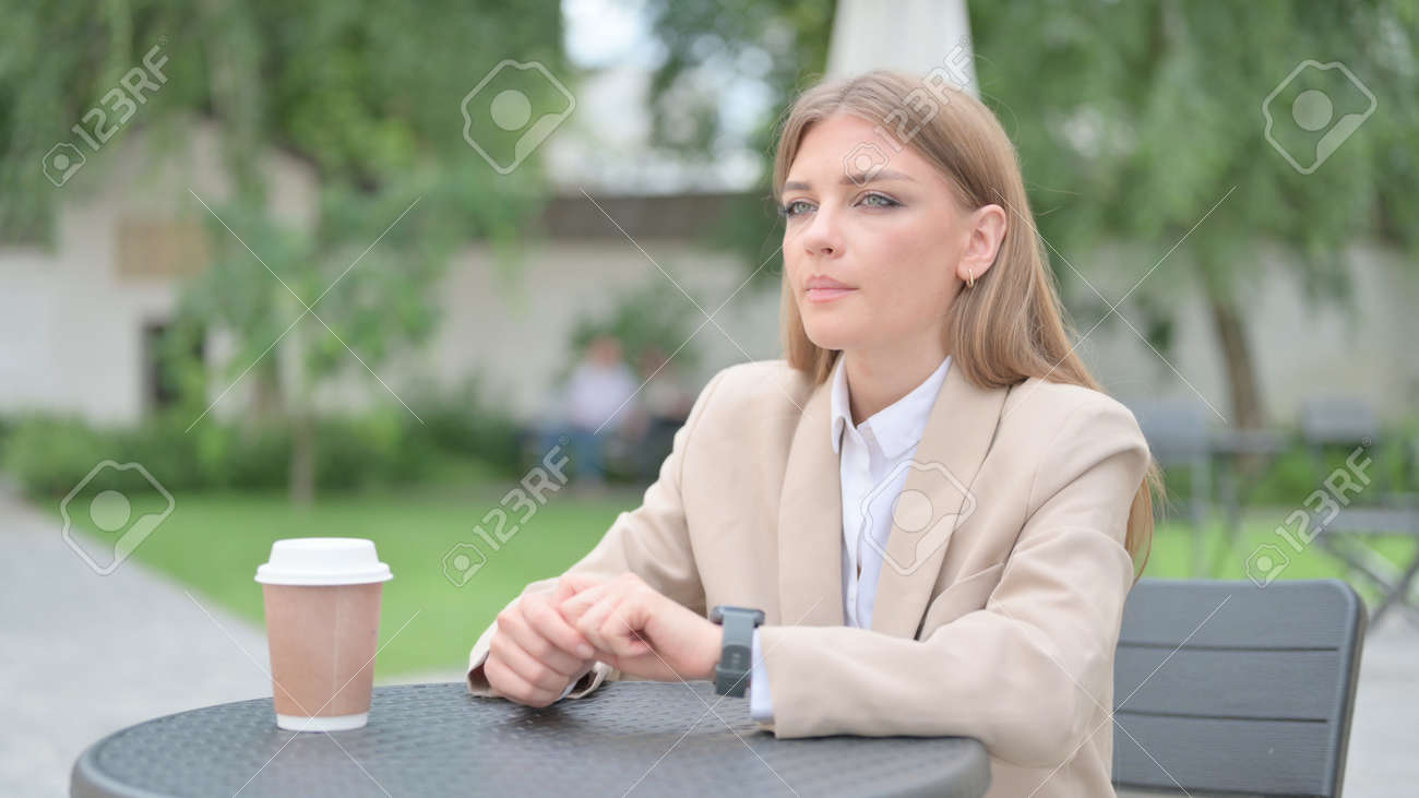 Businesswoman Waiting, Checking Time in Outdoor Cafe - 172195433