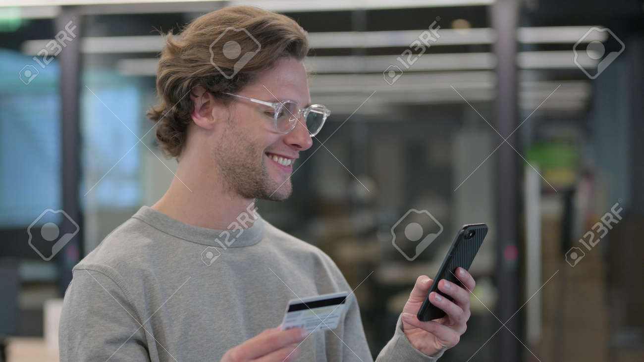 Portrait of Young Man Doing Online Shopping on Smartphone - 172194951
