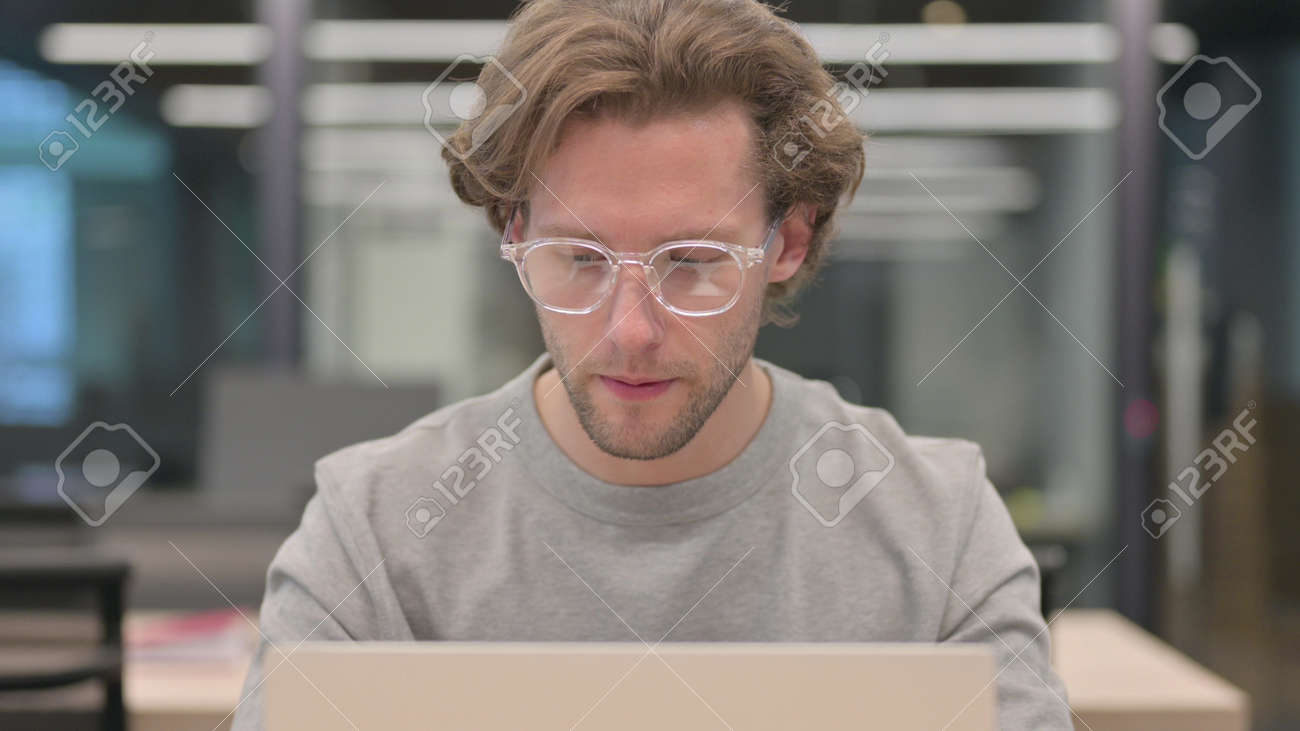 Portrait of Young Man with Laptop feeling Shocked - 172194958