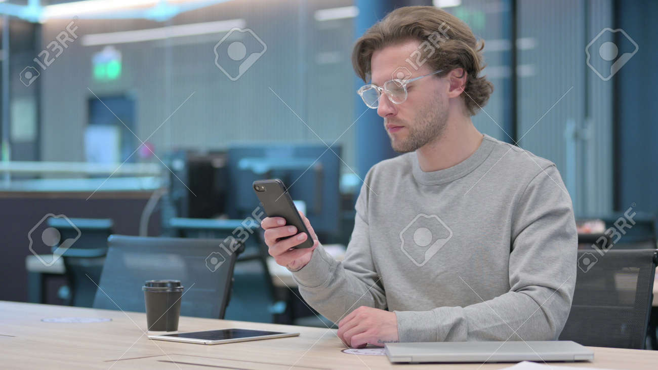 Young Man using Smartphone in Office - 172194959