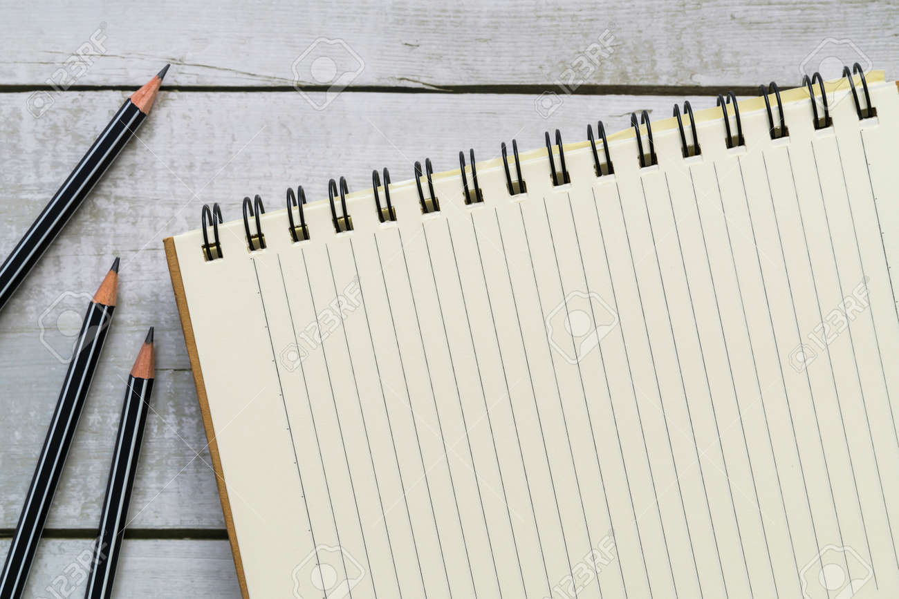 Top view of blank notebook and pencils on white wood table - 170462120
