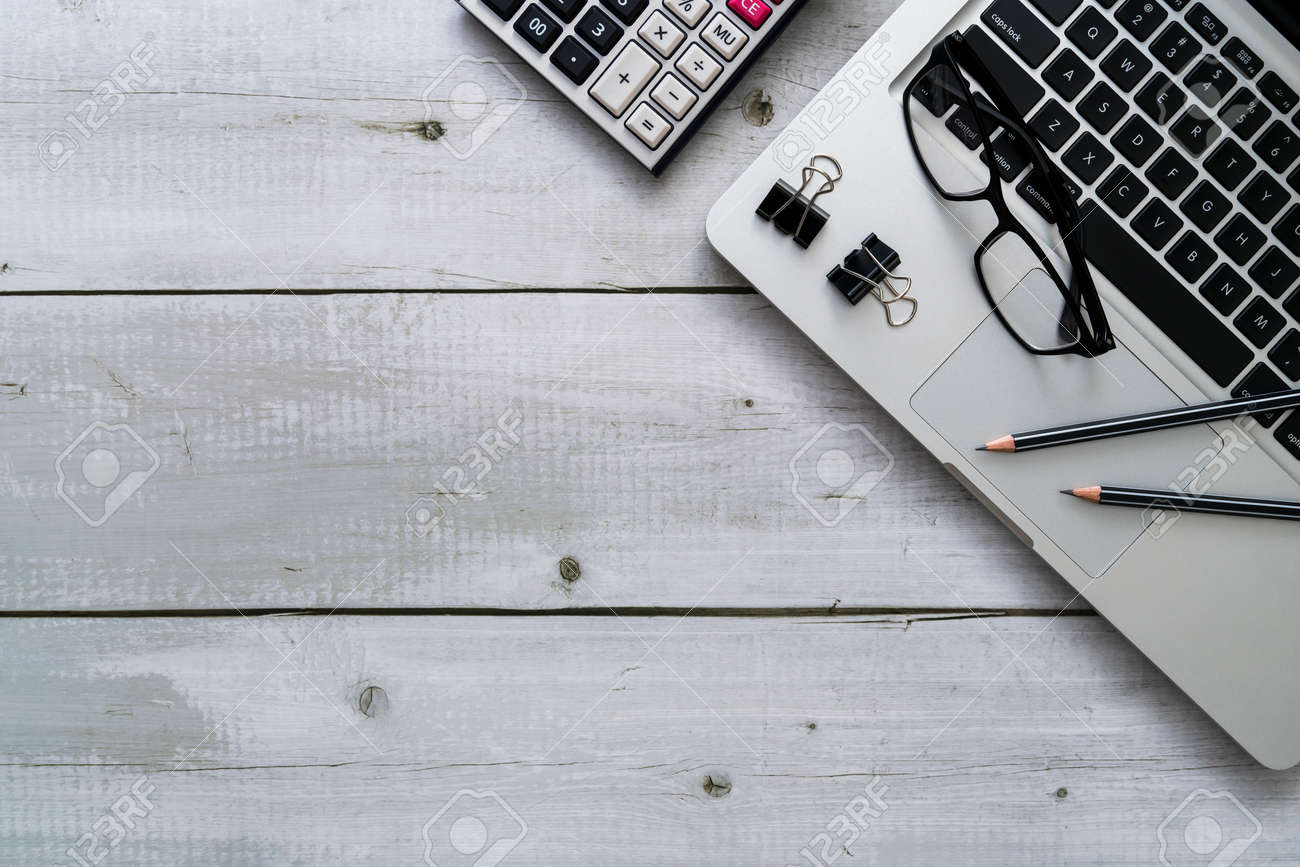 Overhead of office work desk with laptop, pencils, glasses, binder clip and calculator on white wooden desk - 170462119
