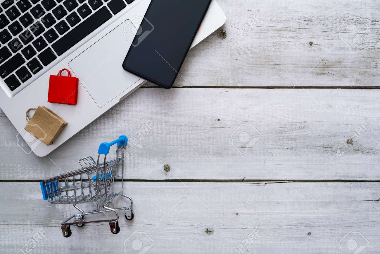 Flat lay for shopping online theme with shopping bag, smartphone on laptop and cart - 170462124