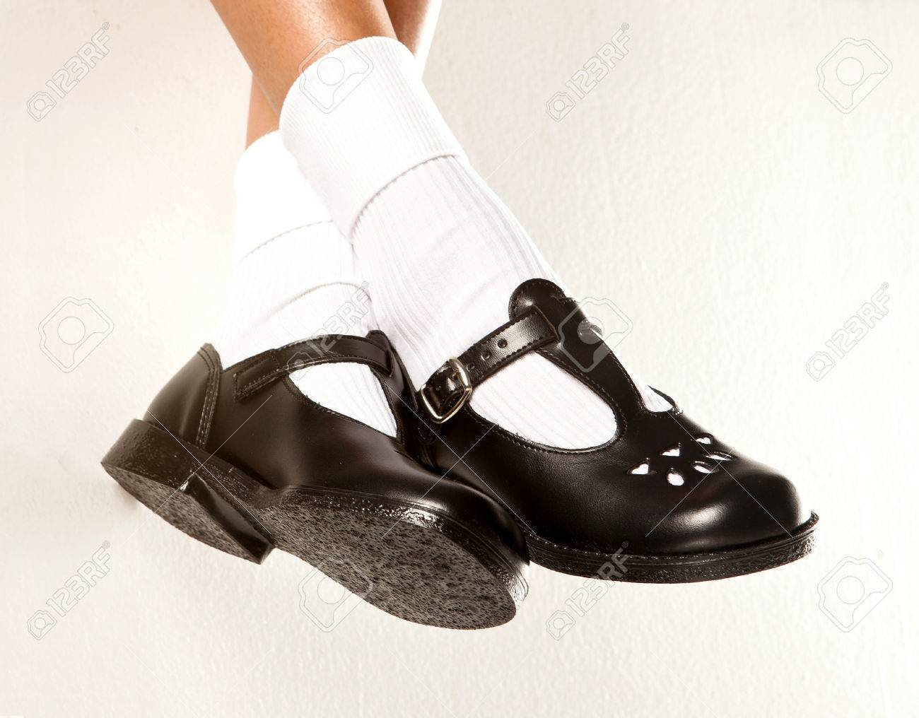 f1b61b6455 A dangling set of kids legs with short white socks and black girls school  shoes on