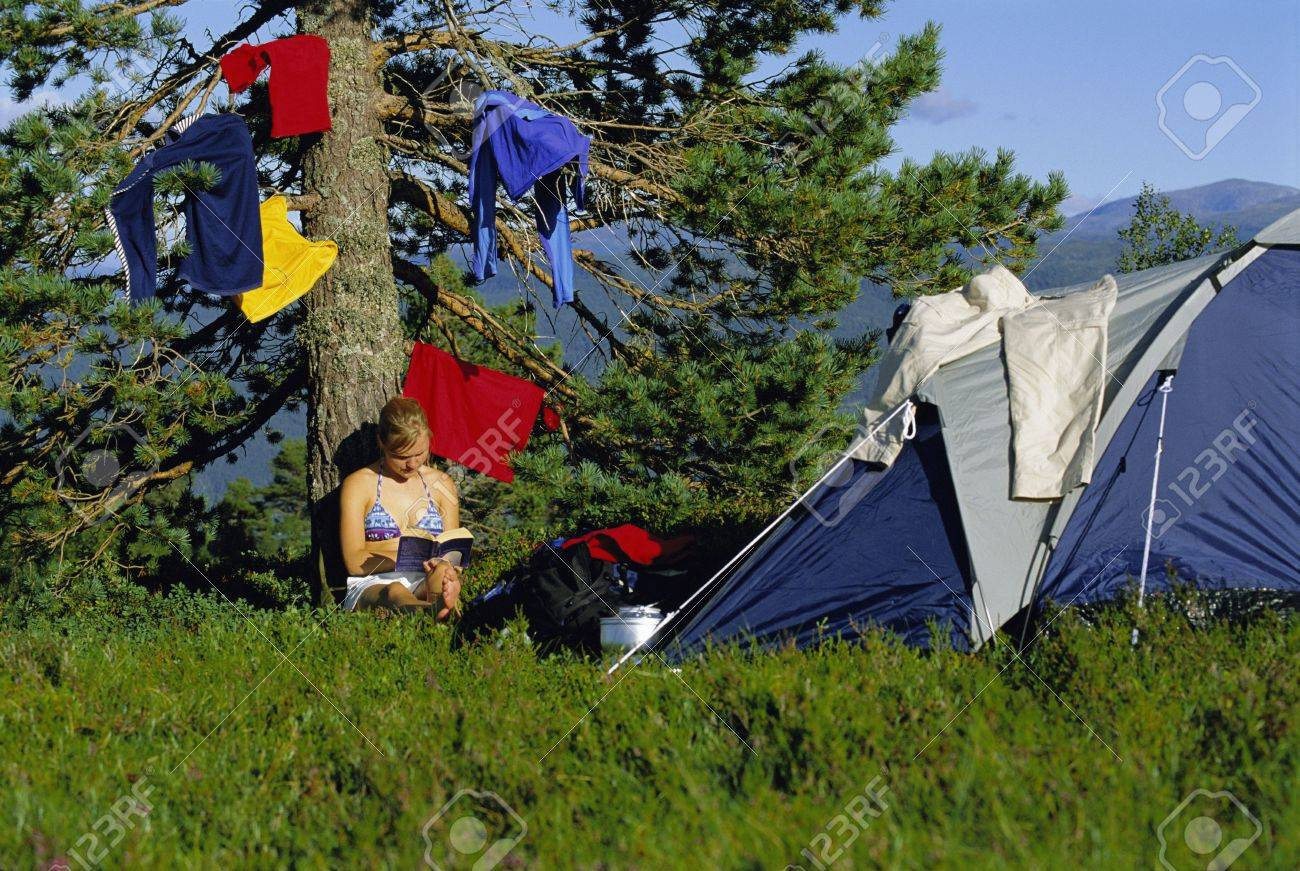 Woman outdoors at campsite reading book by hanging clothes Stock Photo - 3177970