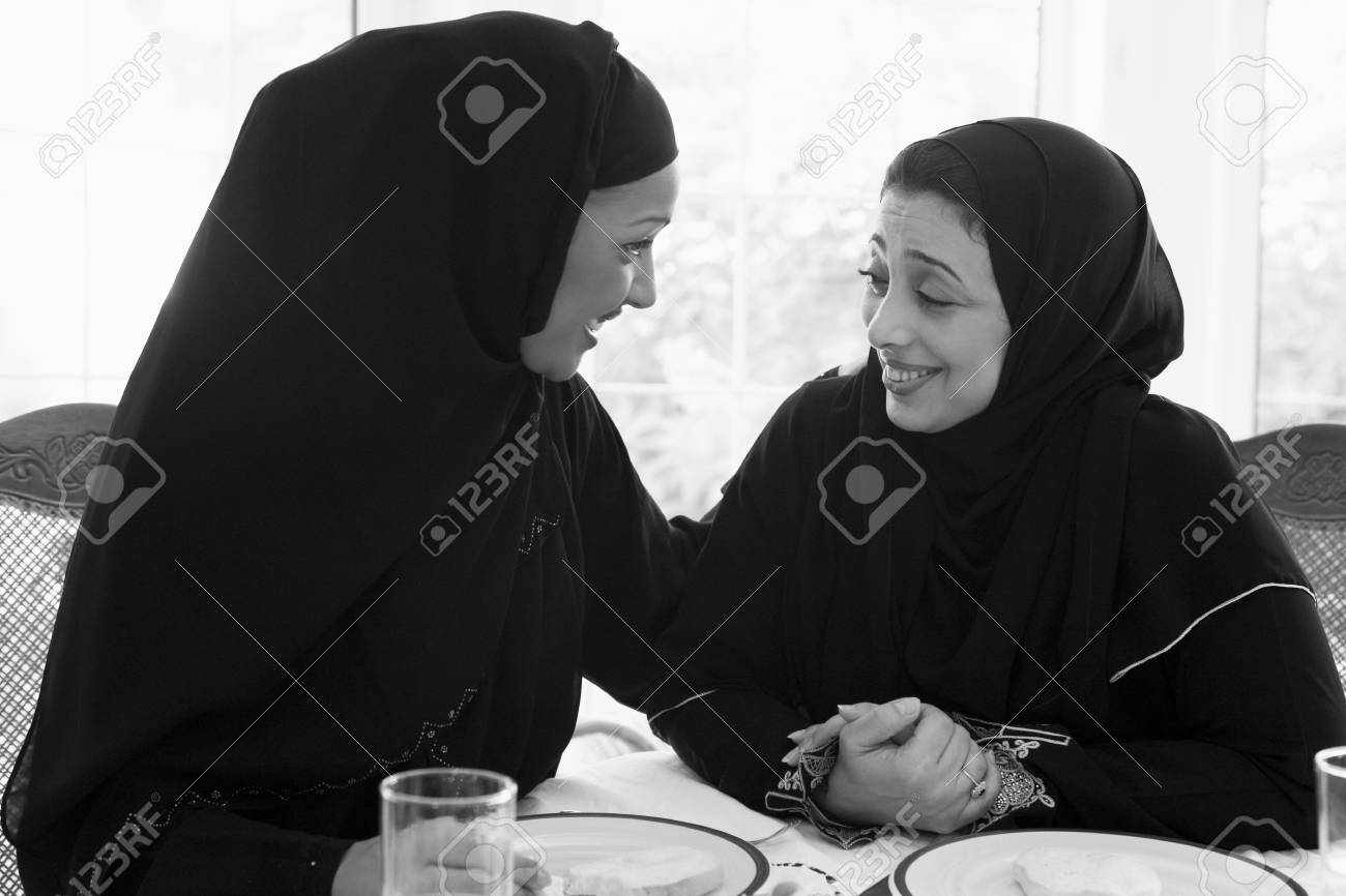 Two women sitting at dinner table smiling (high key) Stock Photo - 3186956