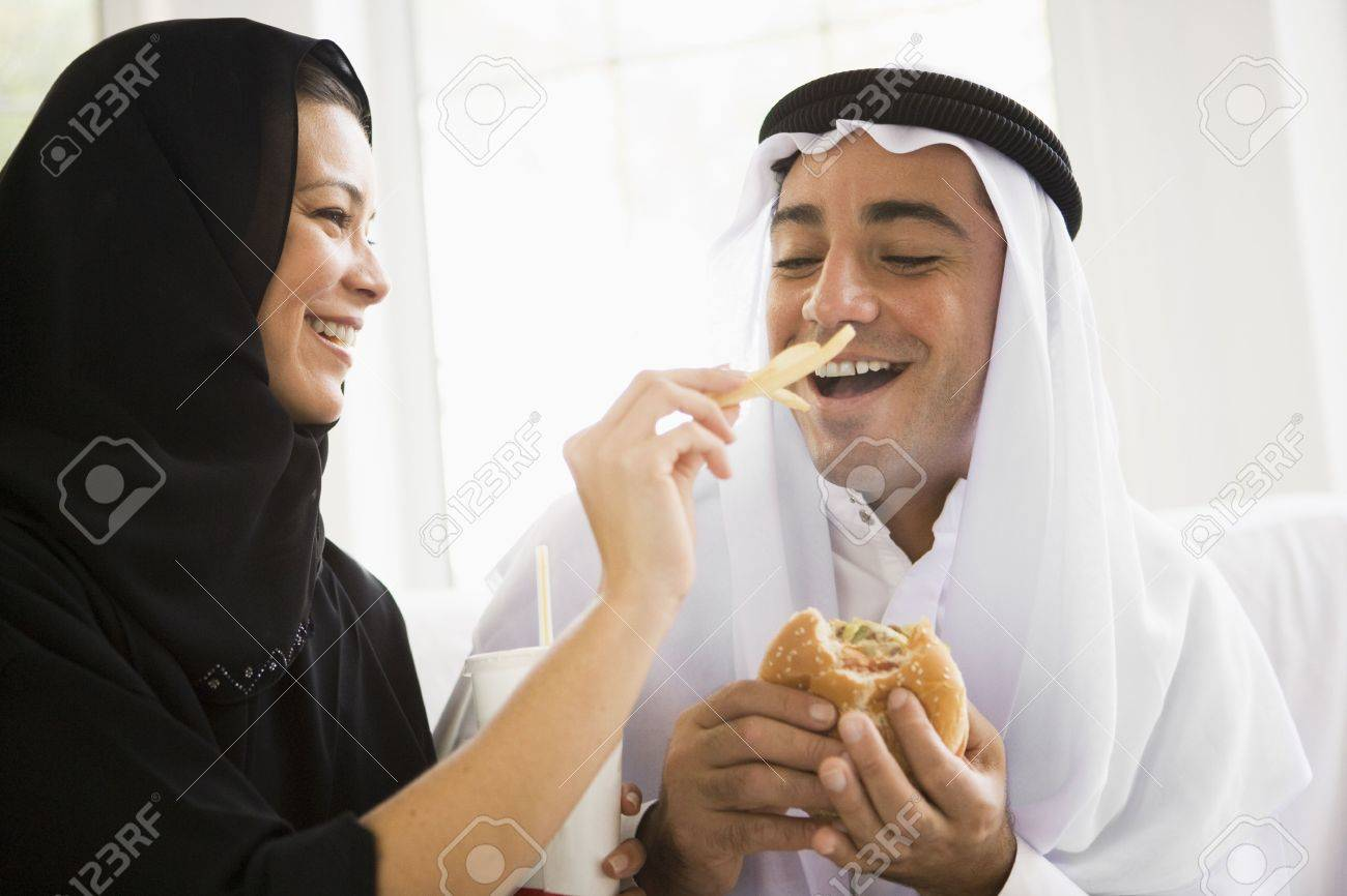 Couple eating fast food in living room and smiling (high key/selective focus) Stock Photo - 3186173