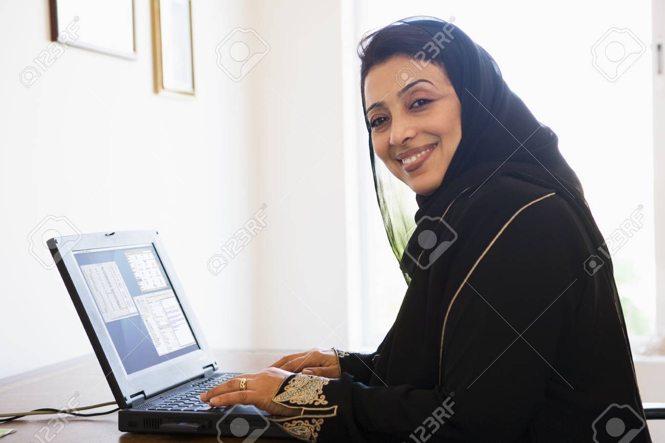 Woman in office with laptop smiling (high key/selective focus) Stock Photo - 3186138
