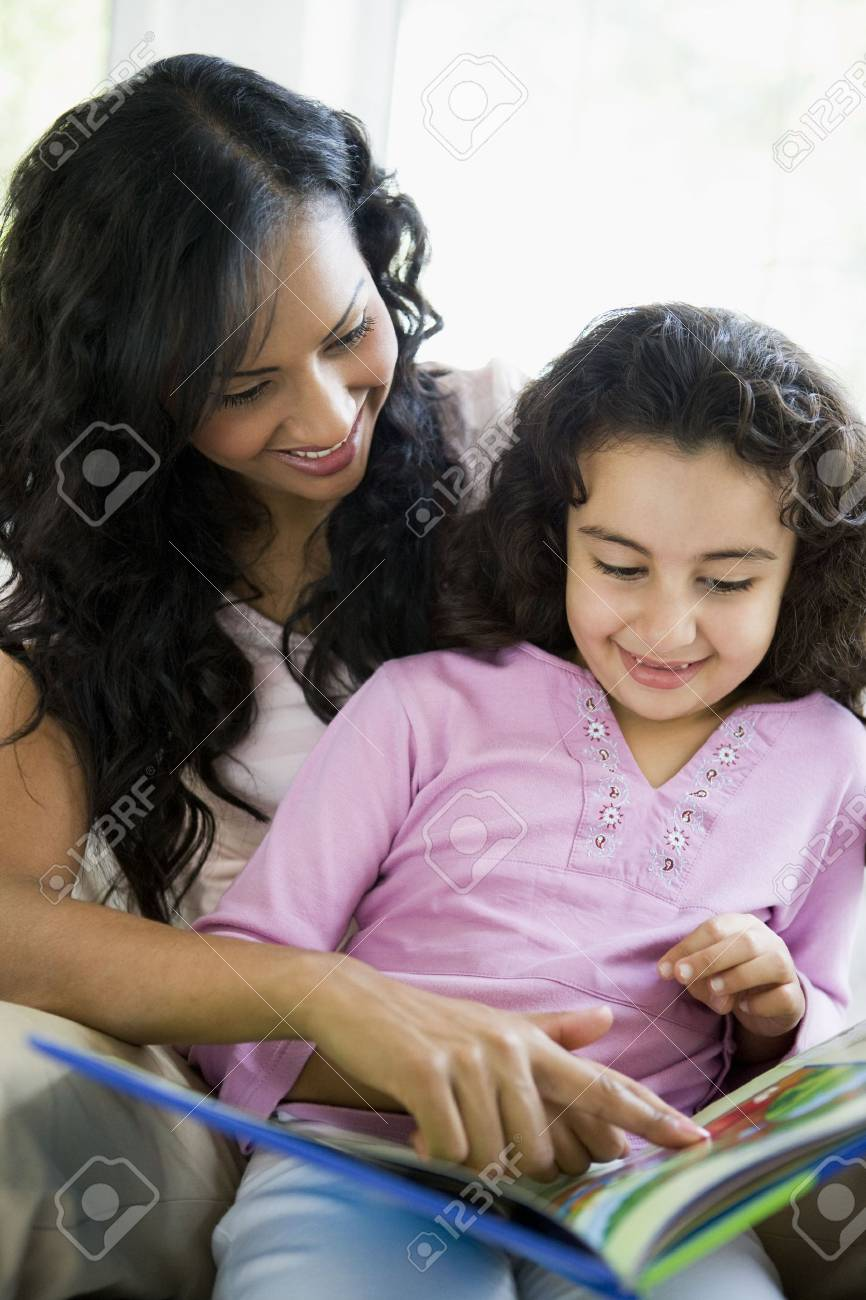 Mother and daughter in living room with book smiling (high key) Stock Photo - 3273921