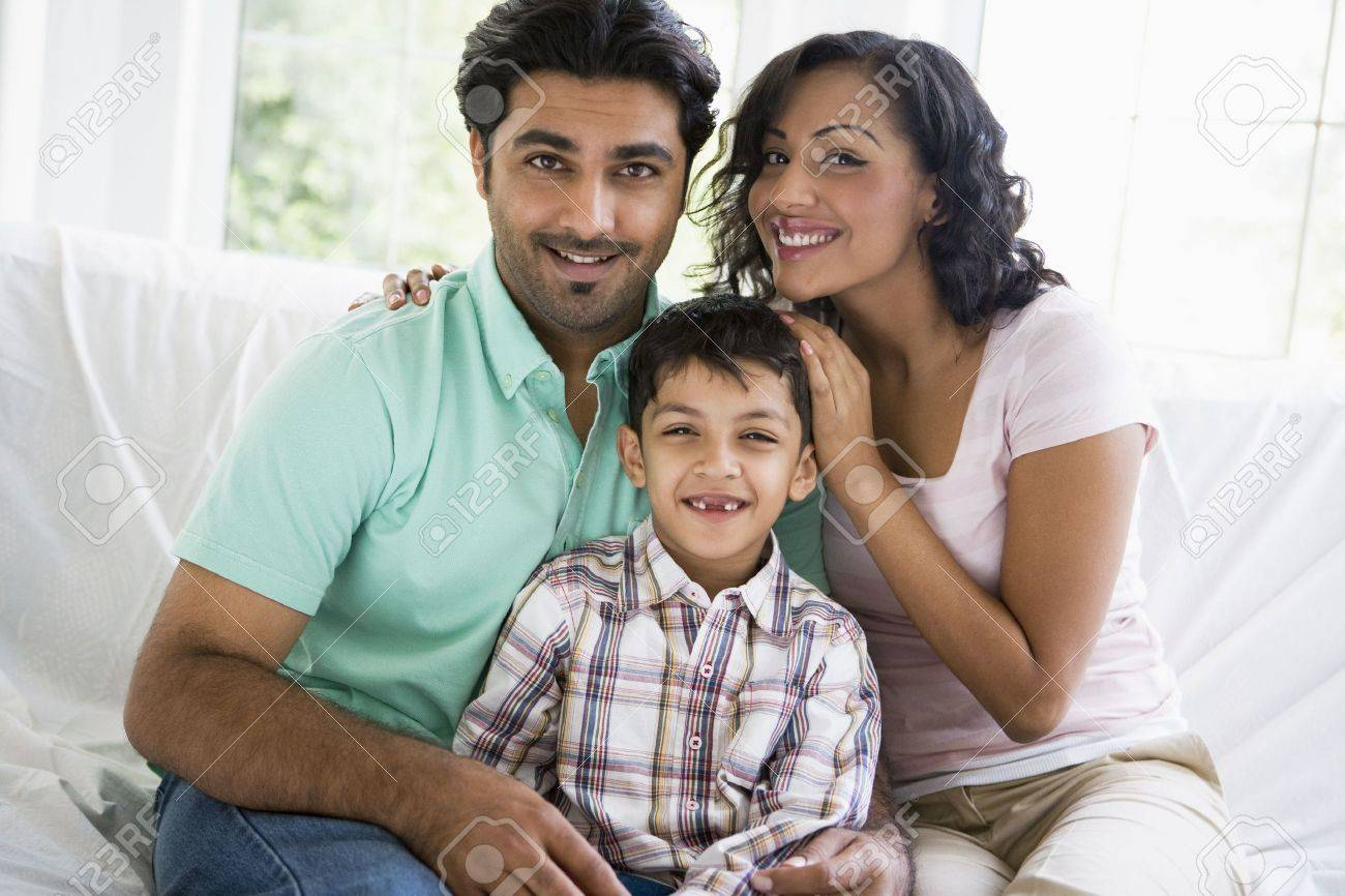 Family in living room sitting on sofa smiling (high key) Stock Photo - 3186288