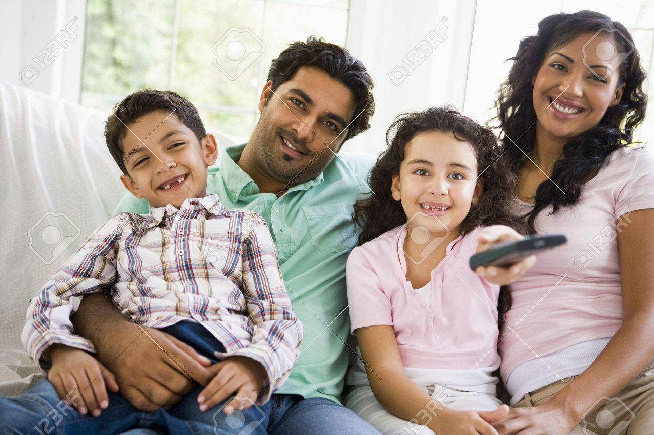 Family in living room with remote control smiling (high key/selective focus) Stock Photo - 3273918