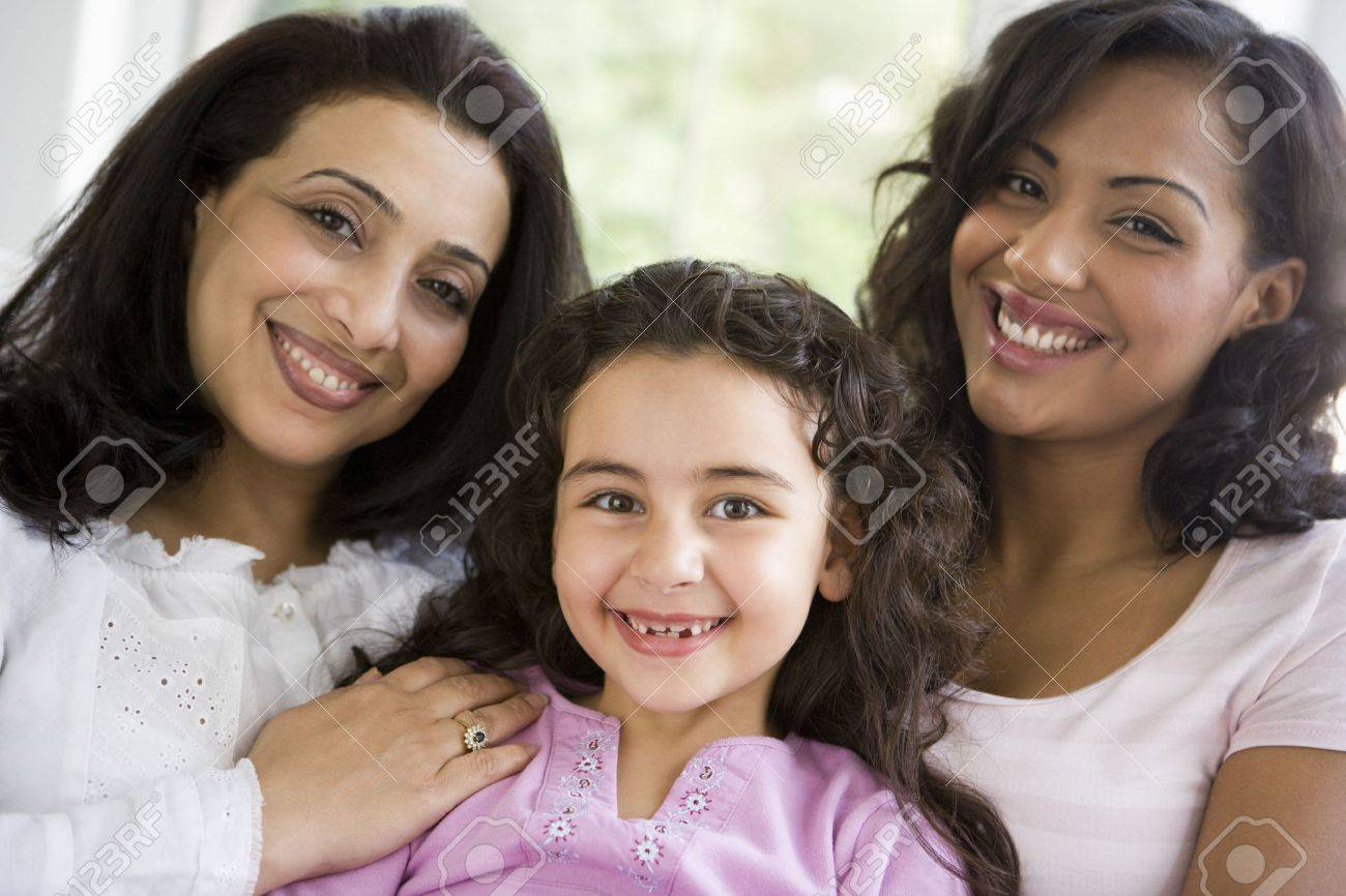 Two women and young girl in living room embracing and smiling (high key) Stock Photo - 3273920