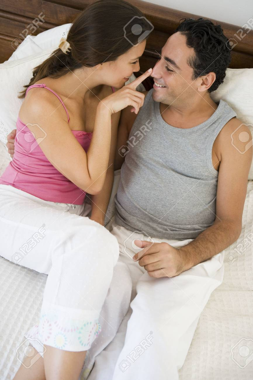 Couple relaxing on bed in bedroom bonding and smiling (selective focus) Stock Photo - 3186306
