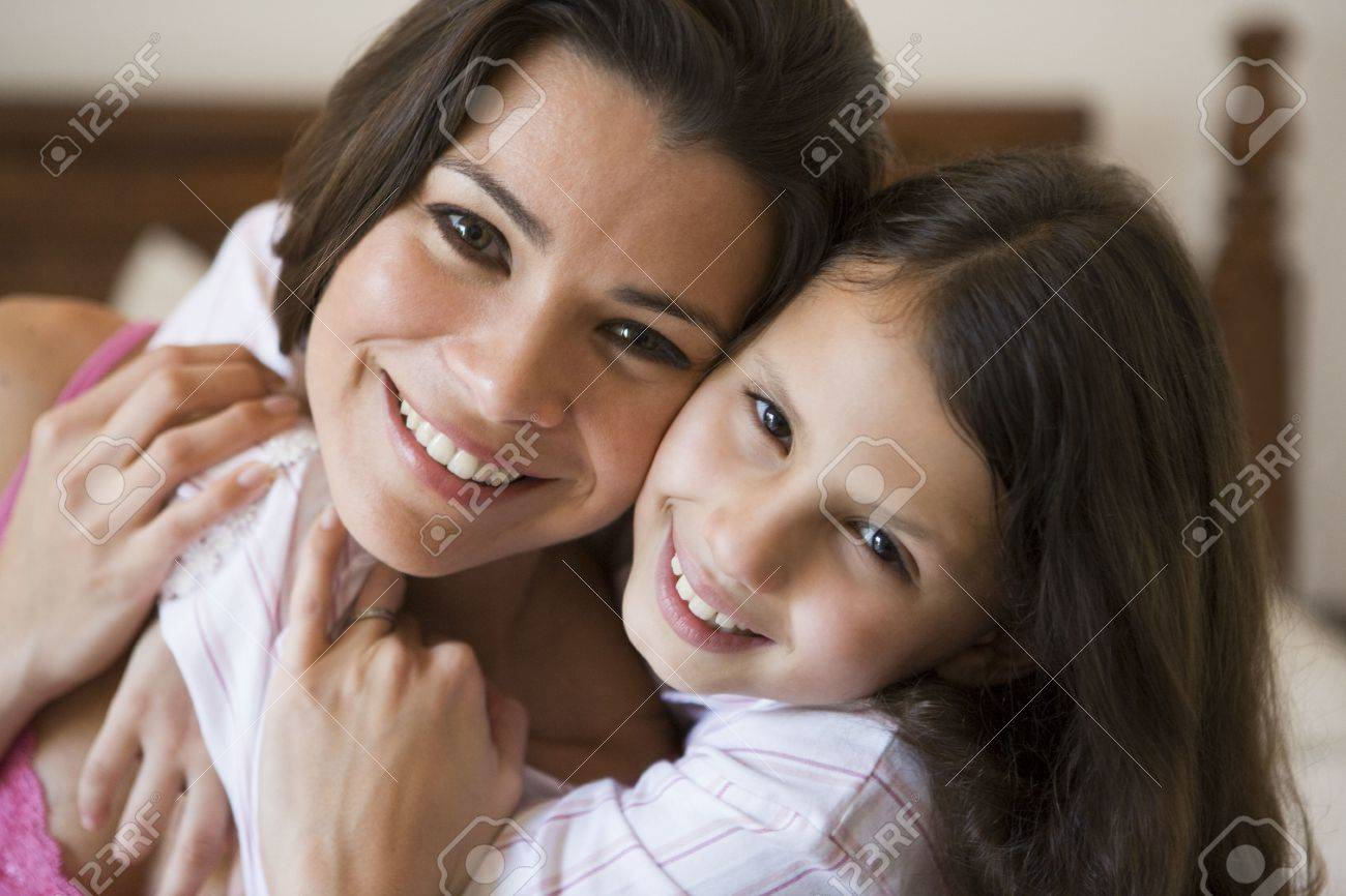 Woman and young girl in bedroom embracing and smiling (selective focus) Stock Photo - 3186562