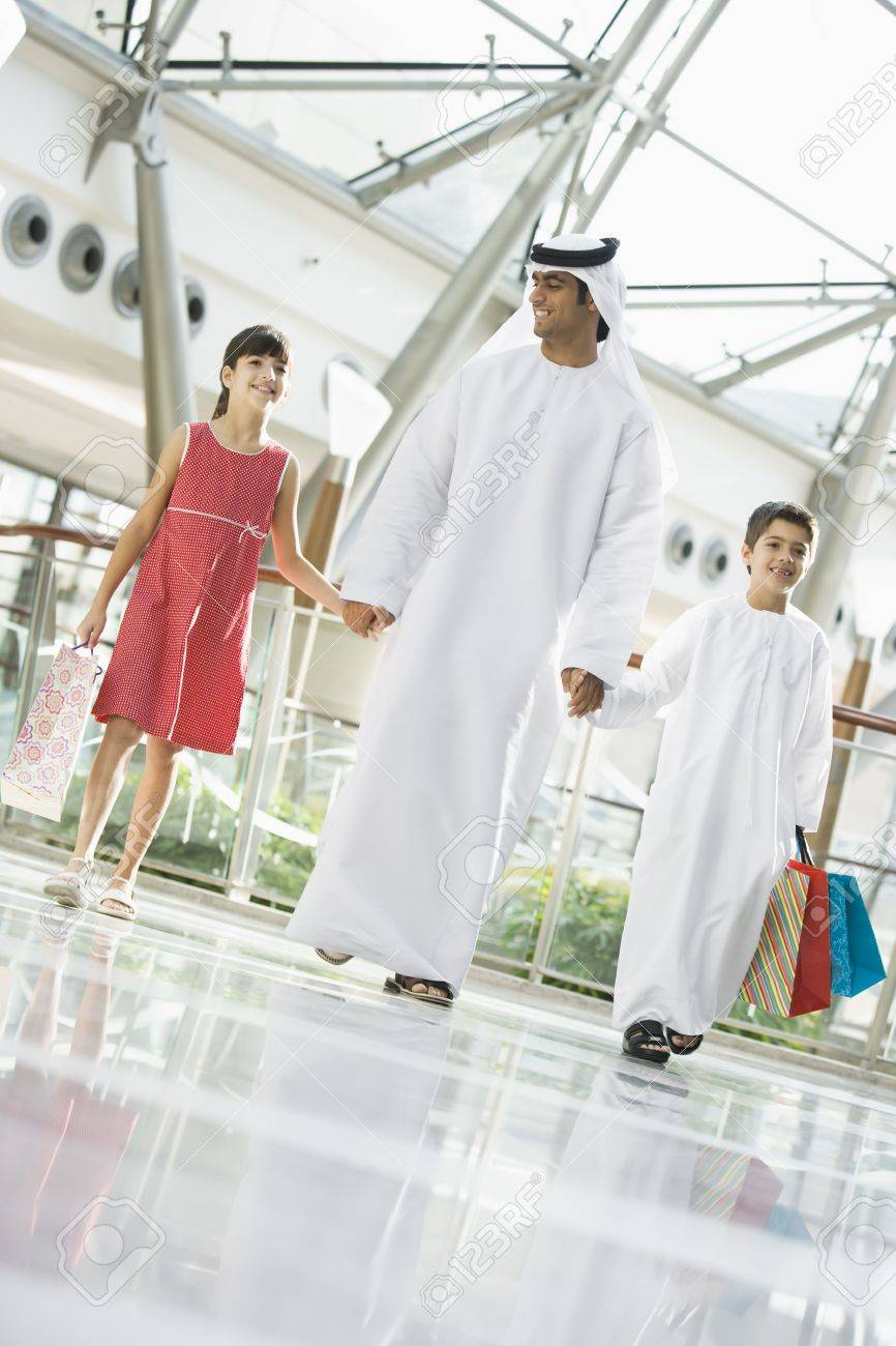 Man and two young children walking in mall holding hands and smiling (selective focus) Stock Photo - 3186757